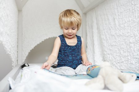 Portrait of beautiful Caucasian baby boy with fair hair dressed in pajamas sitting on white canopy bed, absorbed in reading children's book, looking through pictures with interested expression