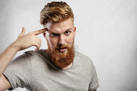Young Caucasian macho man with blond beard and hipster hair-styl