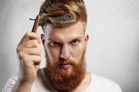 Good-looking young man with red beard holding barbershop accessory. Caucasian barber demonstrating sharp blade of his old-fashioned straight razor, determined to shave clients. Selective focus