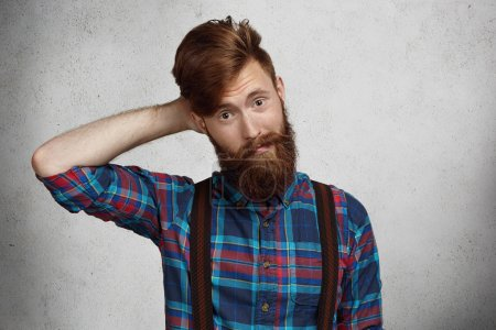 Fashionable hipster with thick beard dressed in trendy checkered shirt and suspenders looking puzzled and confused, holding hand behind his head. Human face expressions, emotions and feelings