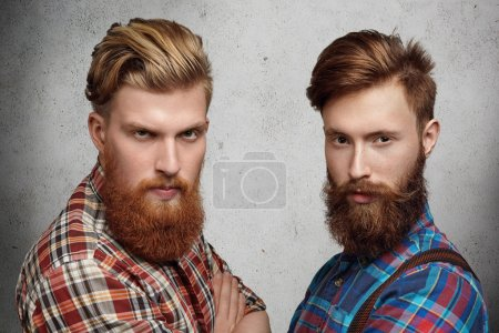 Two handsome young unshaved men with hipster beards dressed in stylish checkered shirts, standing with arms folded on gray concrete wall, looking with serious face expression, squinting eyes