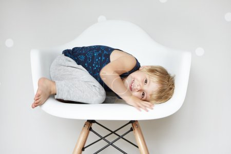 Childhood and leisure concept. Sweet adorable two-year old toddler with cute smile curling up in white chair, hiding himself while playing hide-and-seek with friends at nursery or kindergarten