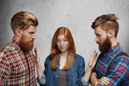Love triangle, adultery, relationships and hard choice problem. Young beautiful woman looking confused and unsure while choosing between two guys. Angry rivals standing face to face, fighting for girl