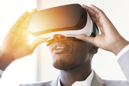 Photo pour Portrait de l'employé de bureau africain étonné ou homme d'affaires à l'aide de casque d'oculus de rift, touchés par réalité virtuelle tout en jouant le jeu vidéo, main dans la main sur des lunettes de protection, à la recherche joyeuse. FLARE soleil - image libre de droit