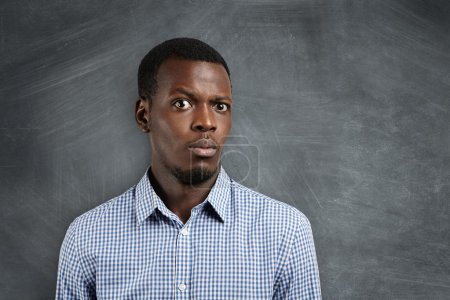 Human face expressions and emotions. Close up shot of doubtful African man dressed casually looking confused and puzzled, raising his brow in surprise and indignation, standing at blank blackboard