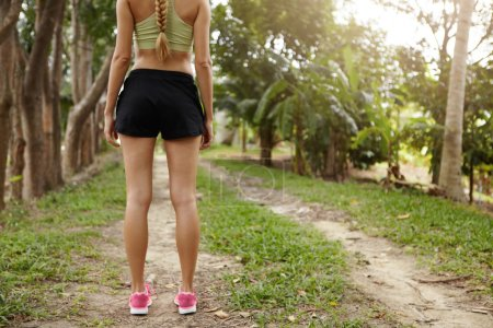 Rear view of young blonde woman athlete in pink running shoes standing in park or forest on path with green trees around. Caucasian girl runner dressed in sportswear preparing for jogging exercise