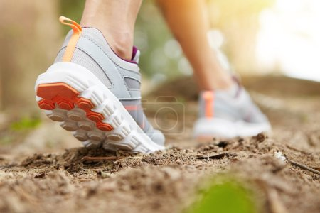 Freeze action closeup of young woman walking or running on trail in forest or park in summer nature outdoors. Athletic girl wearing sport shoes, exercising on footpath. Selective focus on right sole