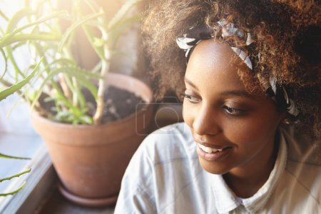 Beautiful young African student girl wearing bandana enjoying free time at cafe after classes at university. Attractive black woman with cute smile relaxing indoors, sitting at window, looking outside