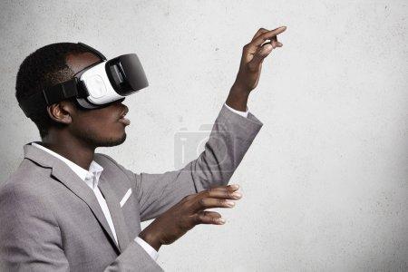 Photo pour Technologie, innovation, cyberespace et des jeux. Voir le profil:: fasciné foncée homme d'affaires en costume élégant, vous le portez oculus rift, gesticulant comme si quelque chose touchant tout en jouant des jeux vidéo - image libre de droit