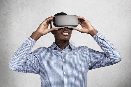 Photo pour Concept de la technologie, l'innovation et le cyberespace. Stupéfié employé africain en chemise bleue s'amuser et se divertir en jouant des jeux vidéo au bureau pendant la pause, utilisation d'oculus rift casque - image libre de droit