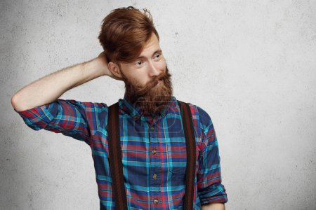 Young doubtful confused bearded man wearing checkered shirt and suspenders scratching his head in uncertainty, looking away with quizzical and questioning expression on his face, thinking of something