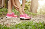 Running sport injury. Female athlete jogger wearing pink sneakers touching her twisted or sprained ankle while jogging or running outdoors. Woman runner massaging her calf muscle before workout