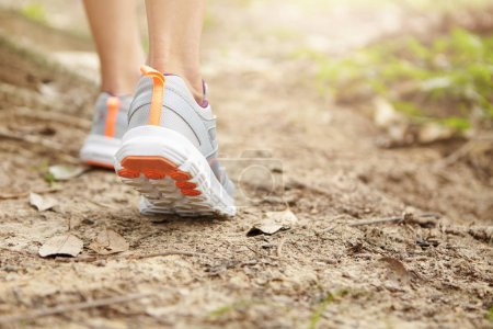 Sports, fitness and healthy lifestyle concept. Freeze action close up of female runner walking or jogging on footpath. Young athletic woman wearing running shoes while hiking in park. Selective focus