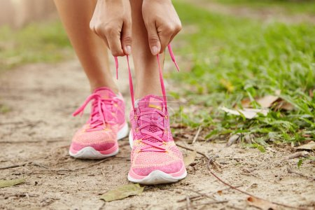 Cropped view of female runner with slim athletic legs lacing pink running shoes, getting ready for jogging exercise in woods. Sporty woman tightening laces of her sneakers, preparing for morning jog