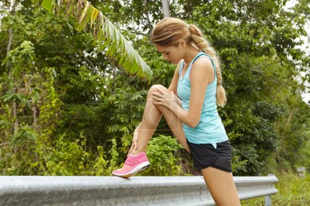 Young athletic woman stretching before morning running workout outdoors. Attractive fit female jogger doing physical exercises as she warming up her muscles, getting ready for jogging on rural lane