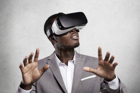Photo pour Jeux, technologie 3d et le cyberespace. Peau foncée entrepreneur en costume formel, l'expérience de réalité virtuelle, jeux vidéo à l'aide de casque d'oculus de rift, gesticulant comme si interagir avec quelque chose - image libre de droit