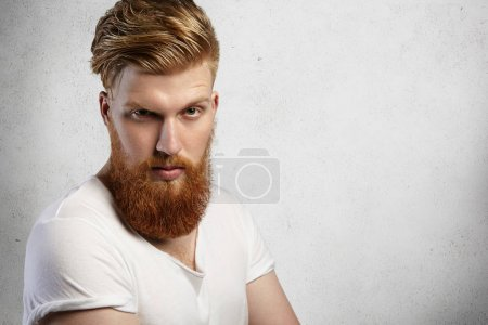 Human face expressions and emotions. Headshot of young model with thick beard posing in studio with angry and unfriendly look. Bearded hipster dressed in white t-shirt with rolled up sleeves frowning