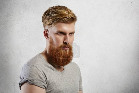 Half-profile studio shot of handsome brutal bearded man wearing gray t-shirt with rolled up sleeves looking ahead of him having serious thoughtful face expression. Hipster model posing isolated