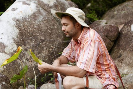 biologist holding leaves of plant