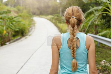 sporty woman standing on road
