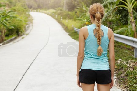 sportswoman with long braid standing on road