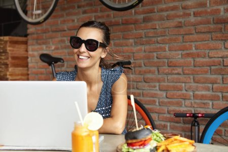 woman having lunch and using laptop