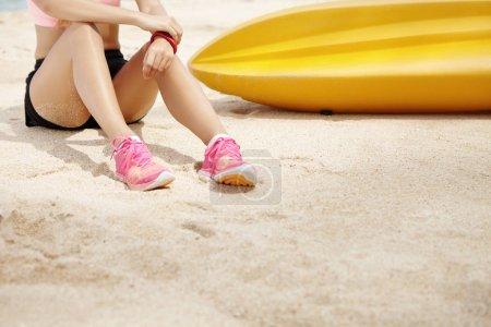 Female runner sitting on sand