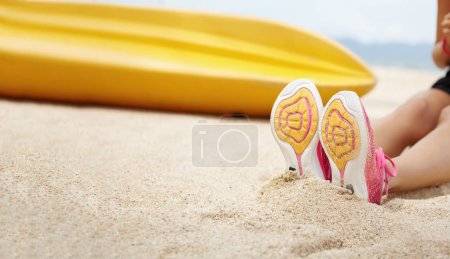 female athlete sitting on sandy beach