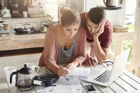 family paying utility bills online using laptop