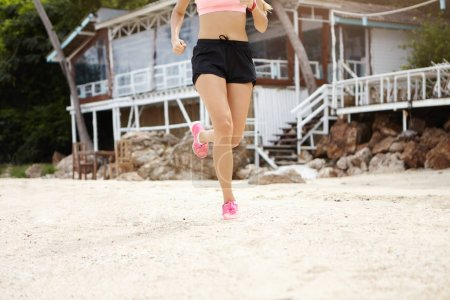 woman runner doing cardio on beach