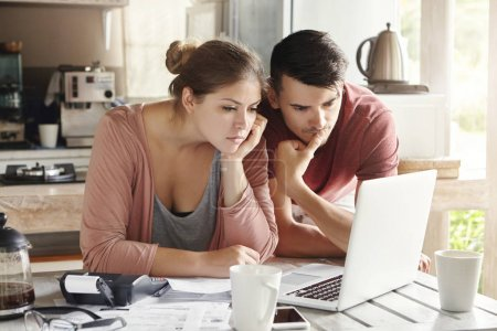 man and woman paying utility bills via internet