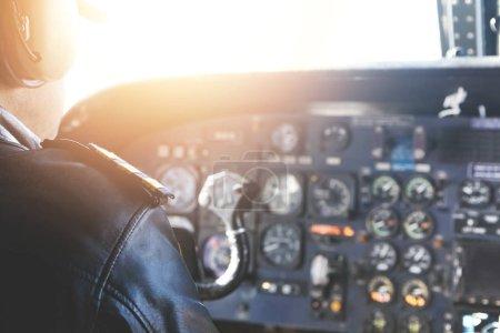 adult pilot sitting inside airplane cabin