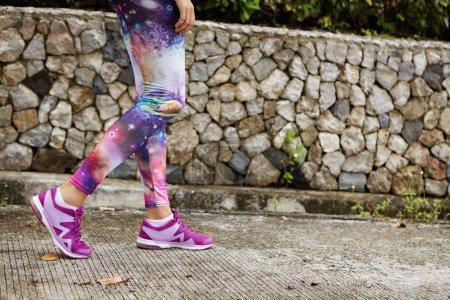 Photo pour Portrait en plein air de femelle coureur avec des jambes athlétiques fit porter baskets violets marche le long chemin de béton dans un parc urbain, attraper son souffle après un entraînement intensif, préparation pour marathon - image libre de droit