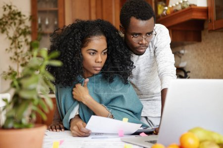 Photo for Financial problems, family budget and debts. Frustrated young African husband and wife using laptop pc while doing paperwork together, calculating expenses, managing bills in their modern kitchen - Royalty Free Image