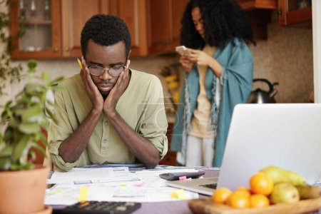 Young African couple facing financial problem not able to pay out debts. Desperate male in glasses holding hands on his cheeks, feeling stressed while managing family budget at kitchen table
