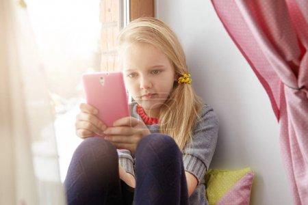 little girl relaxing on windowsill using phone