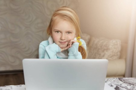 Girl sitting in front of open laptop