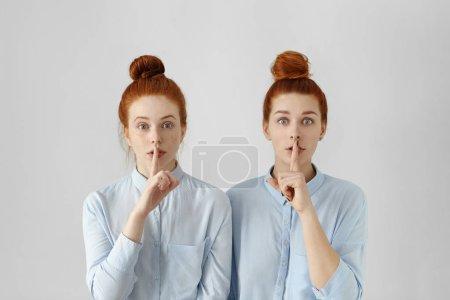 redhead women keeping fingers at lips