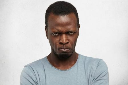 Photo for Studio portrait of displeased, angry, grumpy and pissed off young African American male looking and frowning at camera, pursing lips, having bad mood, feeling dissatisfied and furious with something - Royalty Free Image