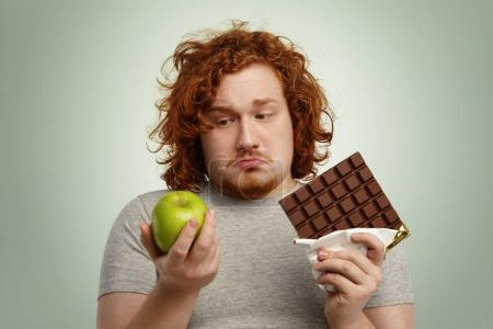male holding green apple and chocolate