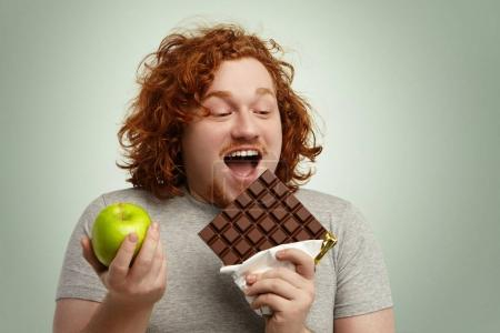 Man holding chocolate and apple