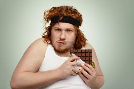 man about to eat up bar of chocolate