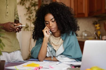 Afro-American woman working through finances