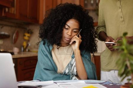 Photo for Candid shot of attractive young African woman in plaid talking on mobile phone while paying bills online and calculating family budget, sitting at kitchen table. Family and financial problems concept - Royalty Free Image