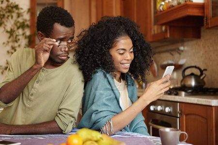 man holding glasses spying his girlfriend's phone