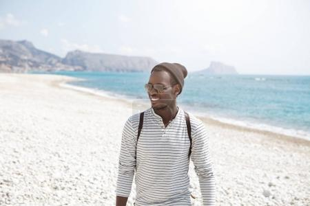 Afro American traveler walk along seashore