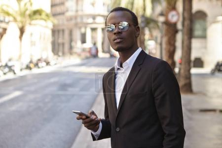 African American entrepreneur on street with smartphone