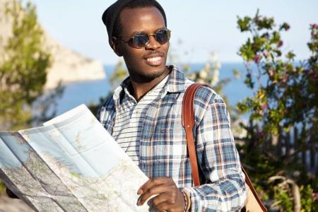 African American backpacker reading map