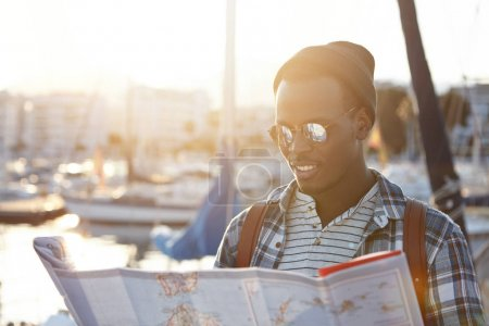 dark-skinned man surrounded by yachts