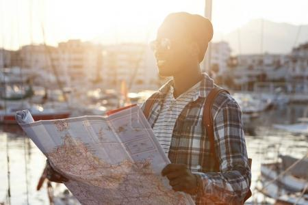 African male tourist holding map
